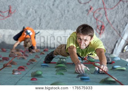 Father and son perform speed climbing relay race on vertical wall. Family Climbing Competitions Mother, Father and Me , Dnipro, Ukraine, September 18, 2016