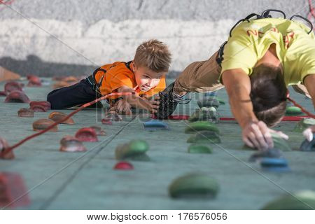 Son touching feet of father in order to hand pass baton during relay race of climbing competitions. Family Climbing Competitions Mother, Father and Me , Dnipro, Ukraine, September 18, 2016