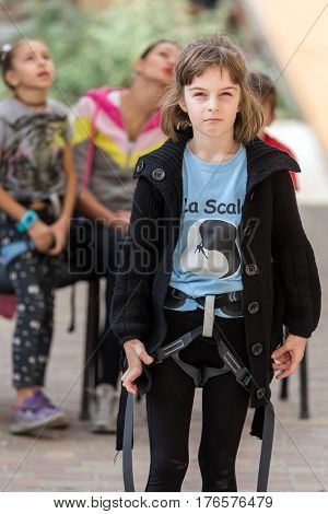 Junior rock climber in safety harness looking straight. Family Climbing Competitions Mother, Father and Me , Dnipro, Ukraine, September 18, 2016