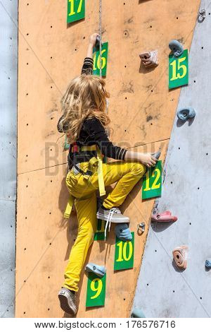 Little female athlete climbs wall on rock climbing competitions
