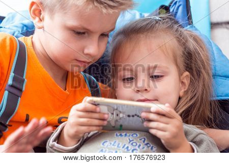 Little boy and girl watching cartoon on mobile device during the break of climbing competitions. Family Climbing Competitions Mother, Father and Me , Dnipro, Ukraine, September 18, 2016