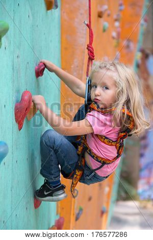 Infant girl in safety harness learning rock climbing doing first steps on vertical wall. Family Climbing Competitions Mother, Father and Me , Dnipro, Ukraine, September 18, 2016