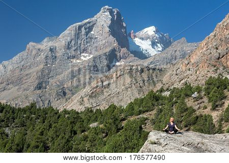 Mountain View and young female doing Yoga exercise on rocky stone