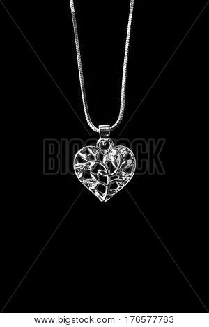 Silver heart pendant hanging on a chain isolated over black