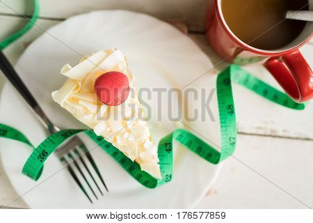 Fancy cake with measure tape and cup of coffee on white wooden background healthy concept