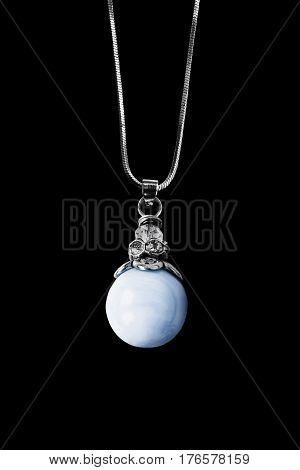 Blue pearl pendant on silver chain isolated over black