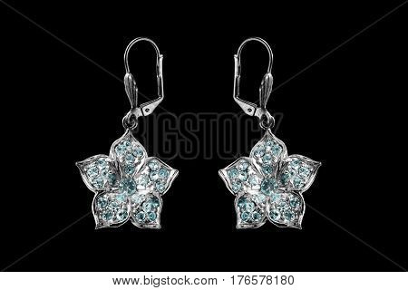 Topaz silver earrings in the form of flowers isolated over black