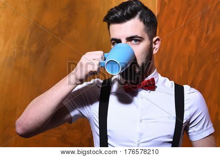 Bearded Man Drinking From Cup Of Tea With Serious Face