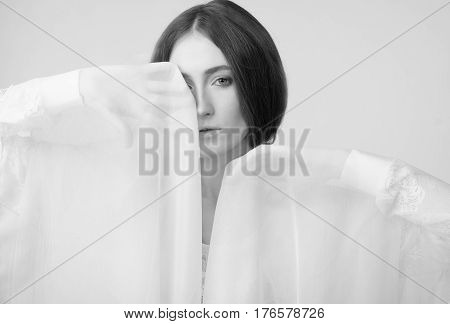 A stylish woman with a transparent shawl near the eyes. Black and White. One eye is covered with a shawl. Scarf beige, emotional movement. Fashion, romance, actress, theater. Light, warm colors.