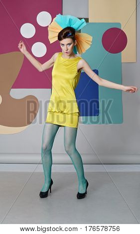 Danish design. A girl in dance. Eccentric girl in a yellow dress, green pantyhose, high heels. Screensaver: circles, rectangles. Multicolor.