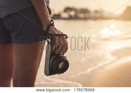 Young woman traveller with retro camera on the beach at beautiful sunset