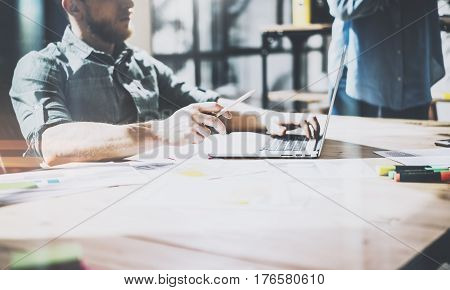 Bearded coworker working at modern office.Man wearing blue shirt and using laptop at the wooden table.Panoramic windows background. Horizontal, film effect.Blurred
