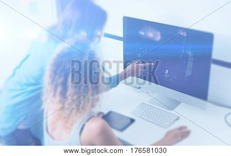 Two young girl working on desktop computer in modern coworking studio.Coworkers using electronics gadgets.Icons, graphs and diagramm on monitor.Visual effect, color filter, blurred.Horizontal