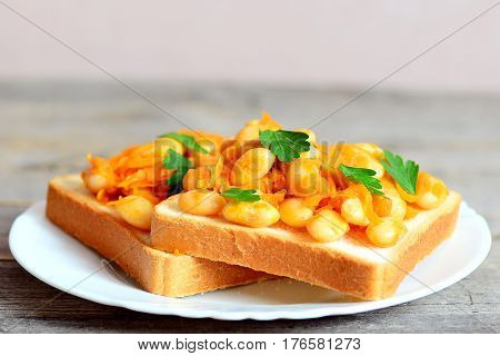 Vegetarian sandwiches with bean. Open sandwiches with bread, stewed white beans and vegetables on a plate. Closeup