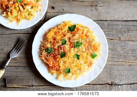 Healthy basmati rice with vegetables and parsley on a plate, cabbage salad on a plate, fork on vintage wooden table. Vegan lunch or dinner recipe. Top view
