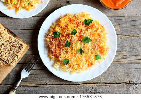 Delicious basmati rice with vegetables and parsley on a plate, vegetable salad on a plate, cracker, pumpkin puree in a bowl, fork on vintage wooden table. Vegetarian lunch or dinner recipe. Top view