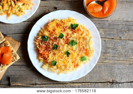 Homemade basmati rice with vegetables and parsley on a plate, vegetable salad on a plate, pumpkin puree in a bowl, cracker with seeds on old wooden table. Vegetarian lunch or dinner idea. Top view