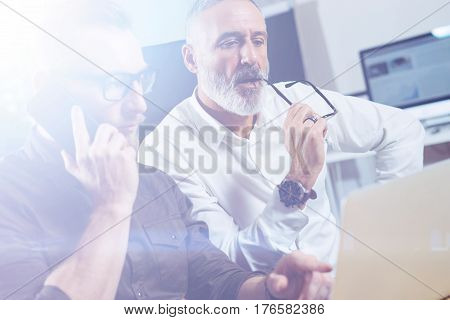 Group of two partners making conference call to discuss a new business idea in modern office.Young bearded businessman making call on smartphone.Business people meeting concept.Visual effects