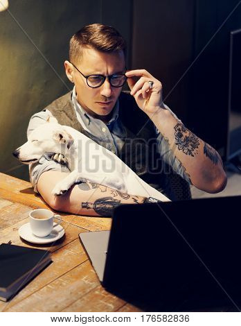 Handsome tattooed man in eyeglasses working at home on laptop while sitting at the wooden table with cute dog on his hands.Adult guy using modern computer for research new business ideas.Vertical