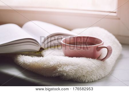 Cozy home still life: cup of hot coffee and opened book with warm plaid on windowsill against snow. Free copy space.