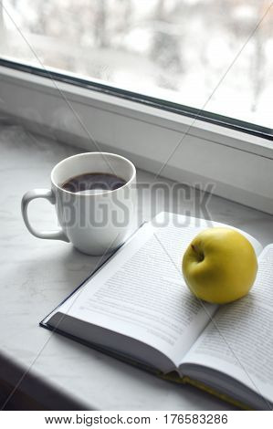 Cozy home still life: cup of hot coffee and opened book with green apple on windowsill. Free copy space.