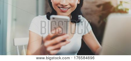 Young smiling Asian woman spending rest time at home and using smartphone for texting with friends.Selective focus. Blurred background, flares effect, wide