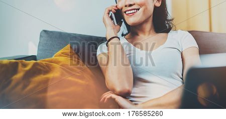 Young smiling Asian woman spending rest time at home on sofa and using smartphone for conversation with friends.Blurred background, flares effect.Wide