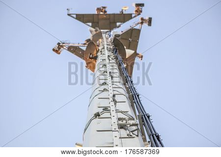 Telephony antenna or base station low angle view with blue sky blackground