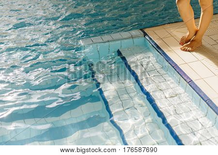 Young woman legs standing on the edge of a swimming pool dipping her leg's in it, on a summer day