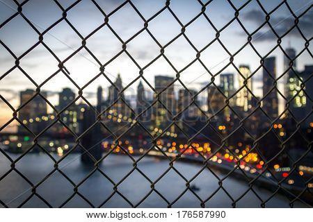 New York City skyline night lights seen through a fence on the Manhattan Bridge NYC