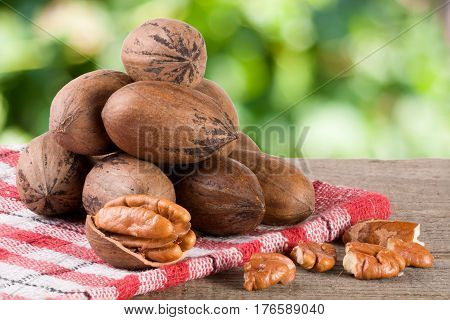 a bunch of pecan nuts on a wooden background.