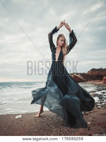 Young Woman In Long Transparent Black Dress Among Beach And Sea.