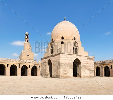 Courtyard of Ibn Tulun Mosque Cairo Egypt. View showing the ablution fountain and the minaret. The mosque is the largest one in Cairo and may be the oldest mosque in the city with its original form