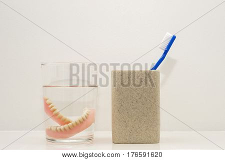 Blue toothbrush in ceramic glass, dental plates in a glass with water at the bathroom