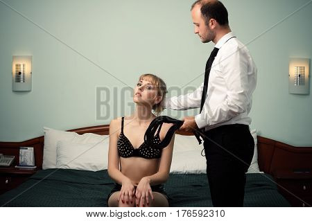 handsome man holding woman hair female slave sitting on the bed