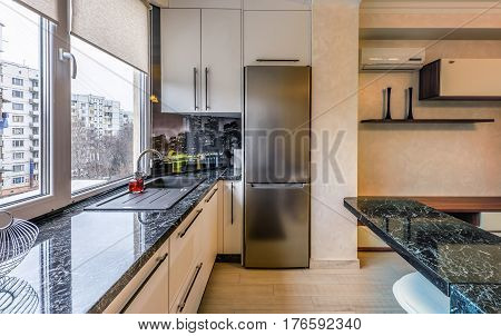 Contemporary modern black colored kitchen with fitted appliances and breakfast bar, window view on buildings at chisinau albisoara street, moldova