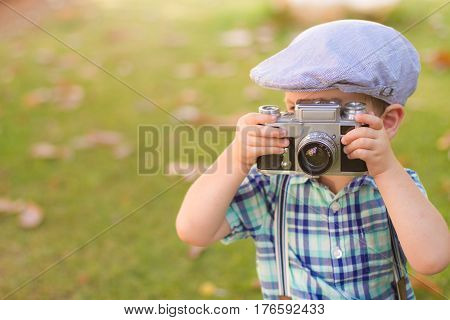 little boy wearing a cap and plaid shirt take photos by a  vintage film camera, shooting outdoor