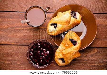 Hot Chocolate With Appetizing Buns. Cherry Jam In A Glass Vase. Sweet Buns With Blueberry Jam On Woo