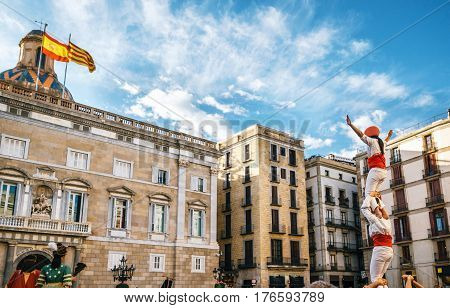 The Castellers de Barcelona of the Corpus Christi festival stand in front of the historical town hall with Giant puppets Gigantes and viewers.