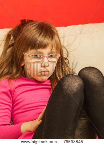 Boredom vision eye problems concept. Young toddler girl wearing glasses sitting on sofa indoor