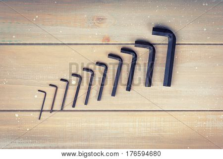 Old hex keys are laid out from the smaller to the larger on a wooden background