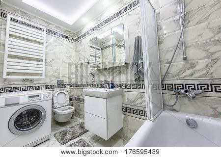 Stock photo white and black small bathroom with washing machine, bathtub and mirror, chisinau, moldova