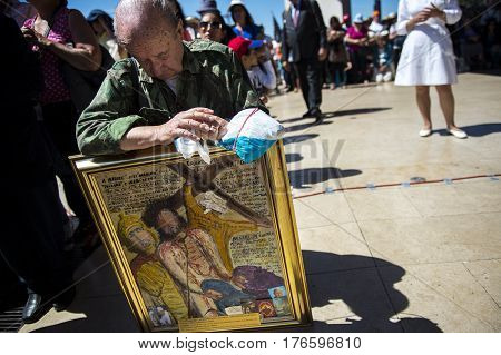 Fatima Portugal - May 13 2014: Man with a painting of Christ praying at the Sanctuary of Fatima during the celebrations of the apparition of the Virgin Mary in Fatima Portugal.