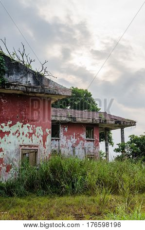 Ruined mansion surrounded by lush green with dramatic sky. Traces of the civil war in Robertsport, Liberia.