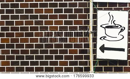 the coffee symbol on white signage plate with the brick wall facade.
