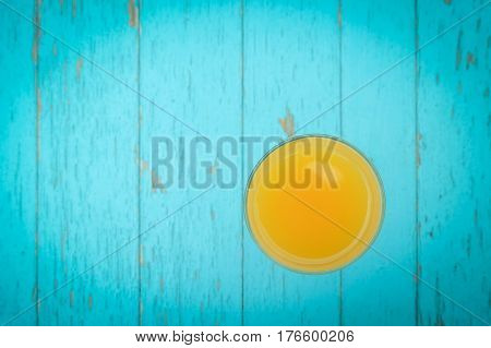 Glass of orange juice on blue wooden table. Blue wooden food background. Flat lay. Shallow DOF