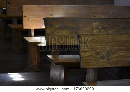 The wooden benches inside a Catholic Church