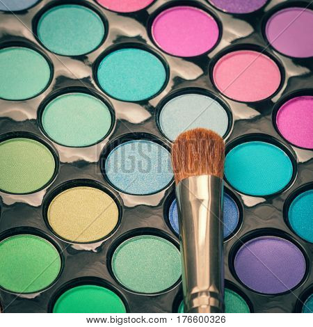 Flat lay of makeup brush with colorful makeup palette