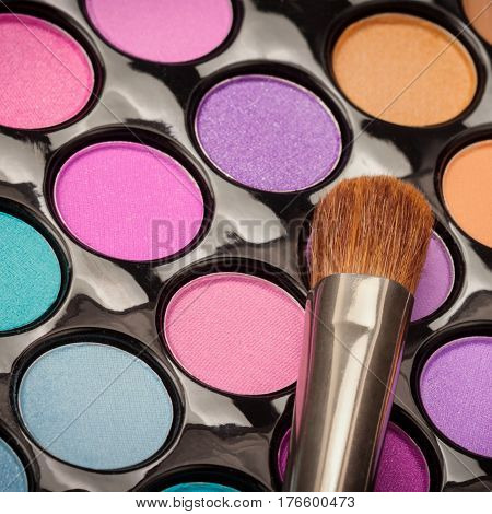 Macro of makeup brush with colorful eyeshadow palette