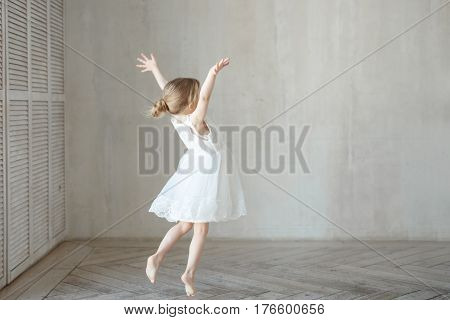 Little girl is playing in a room in a beautiful dress